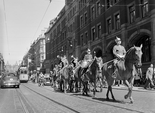 FOTOGRAFI Kungliga Livgardesskvadronens (K1) musikkår till häst blåser in Nationaldagen. De rider söder ut på Vasagatan. 1950-1950 FOTOGRAF: Karlsson, Yngve. Svenska Dagbladet BILDNUMMER: SSMSvD024850 Stockholms stadsmuseum, Sweden